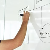 Photo of arm drawing diagram on whiteboard